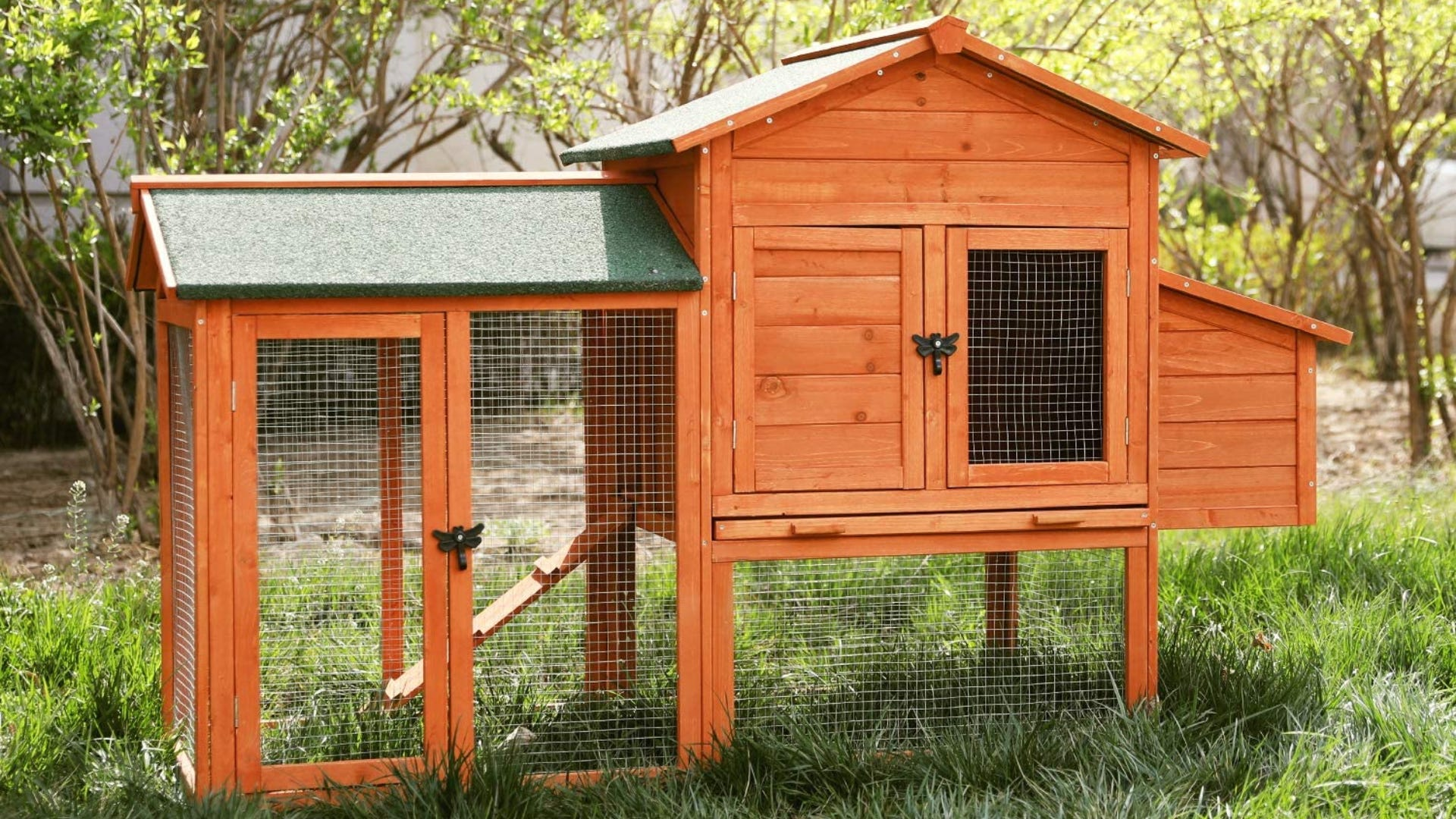 Wooden chick coop set up outside in a sunny, green garden.