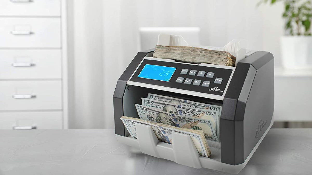 A bill counter processing a large stack of bills on a table