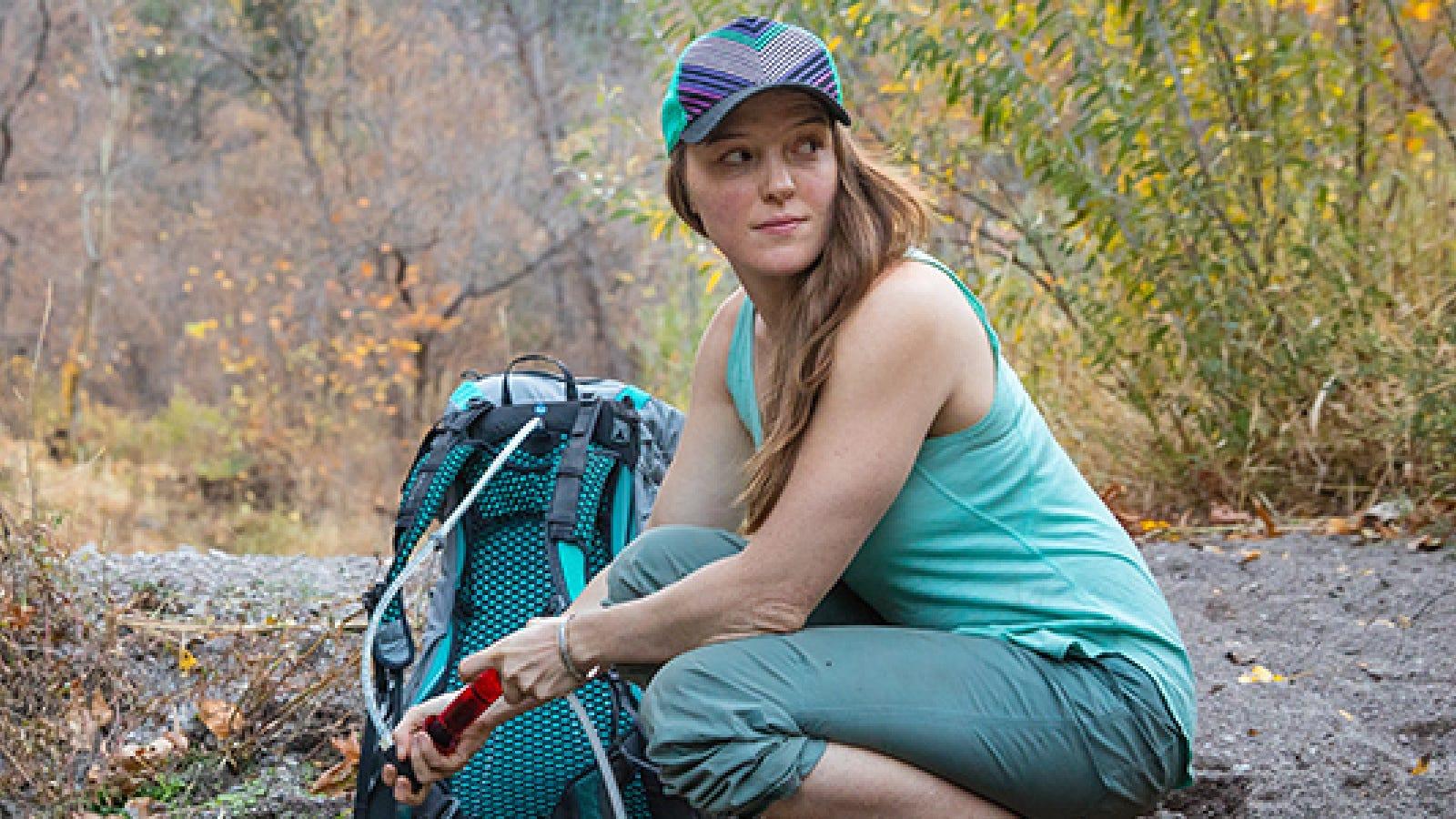 A hiker filling her Osprey hydration reservoir on a hiking trail.