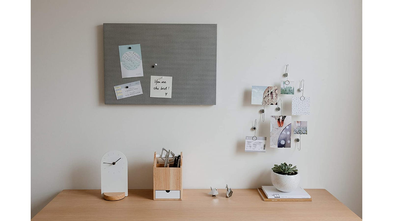 A grey bulletin board with notes pinned on it is mounted above a decorated wooden desk.