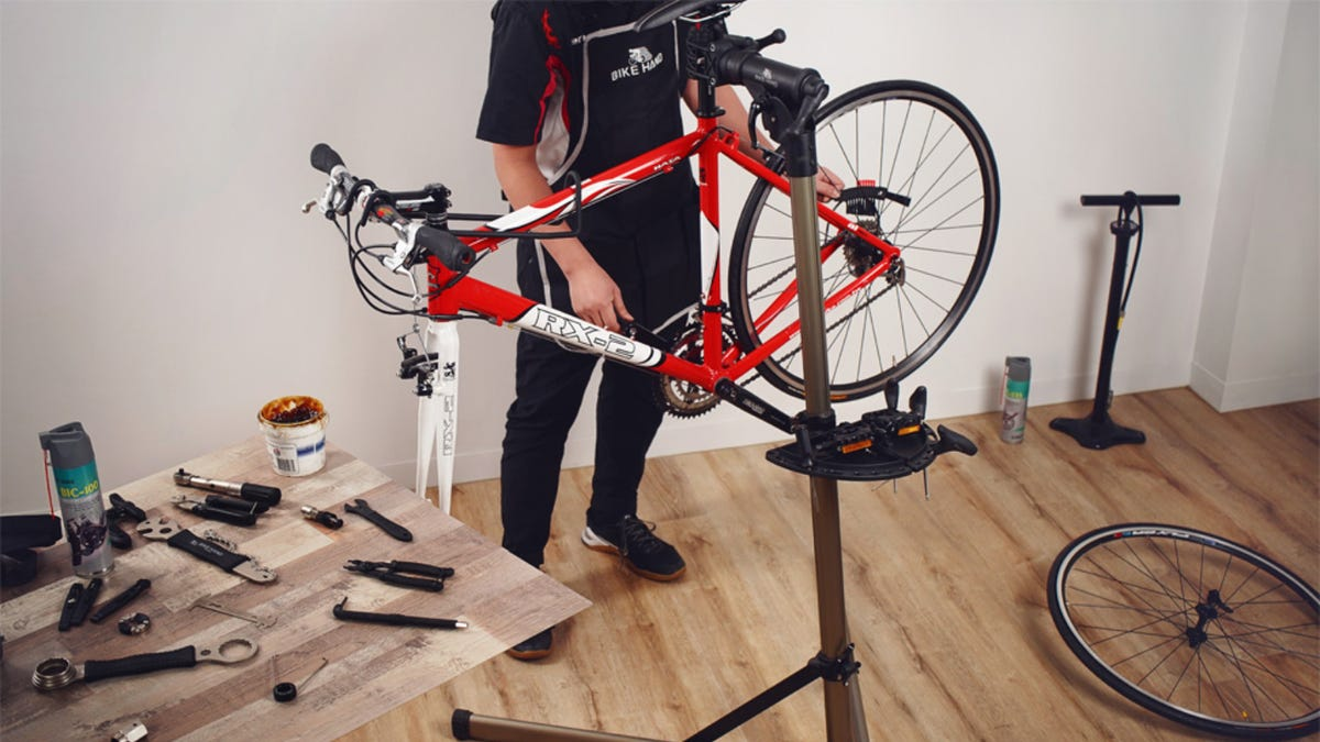A man working on a red bike that is held by a bike stand.