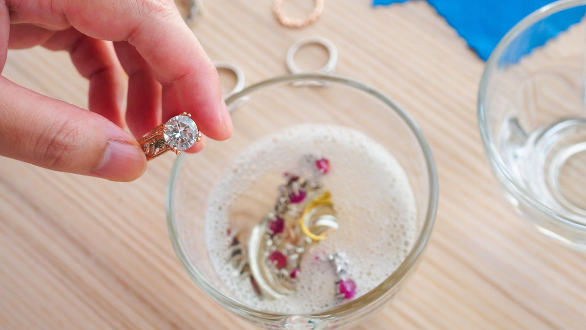 Close up of a hand cleaning a vintage jewelry diamond ring over a clear cup of soapy water.