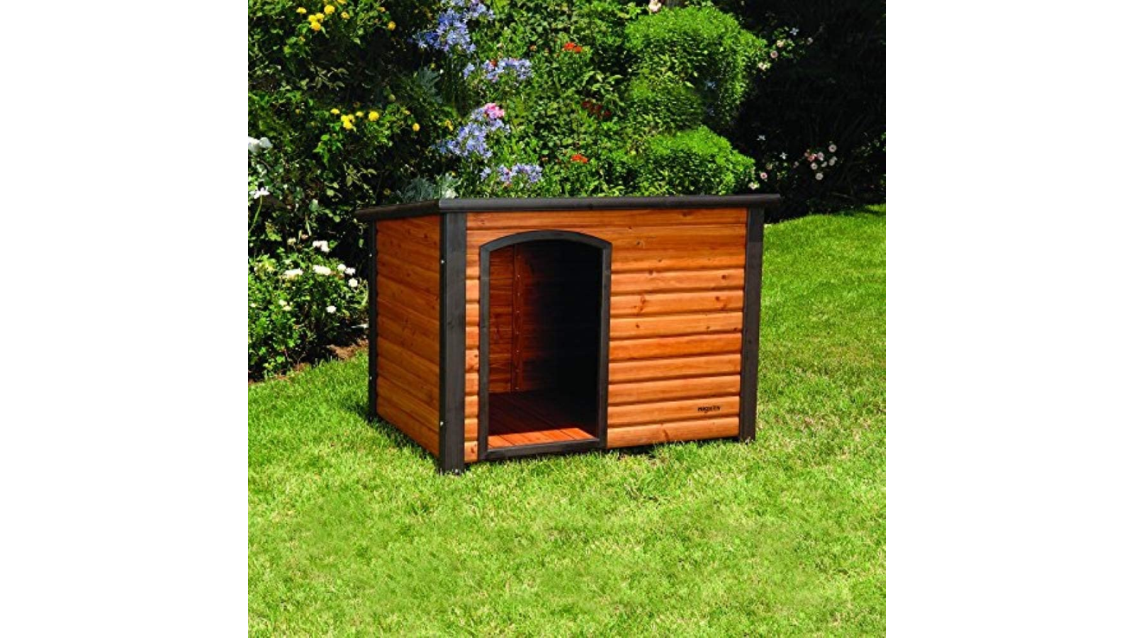 Wooden doghouse placed outside on green lawn.