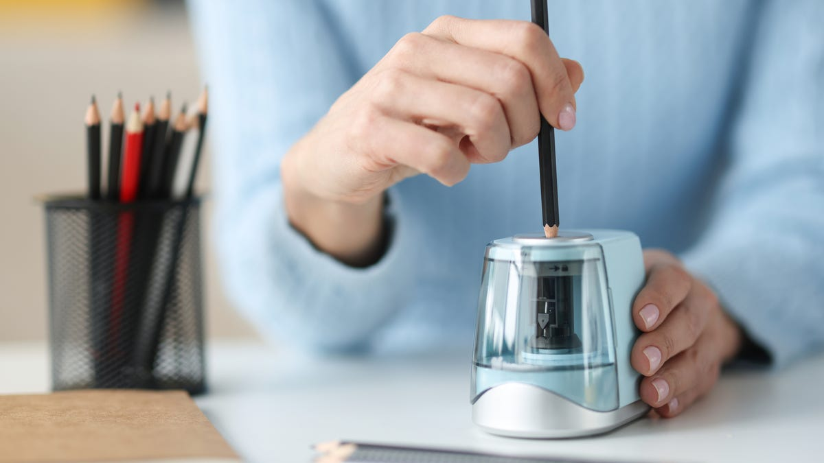a woman using an electric pencil sharpener at her desk