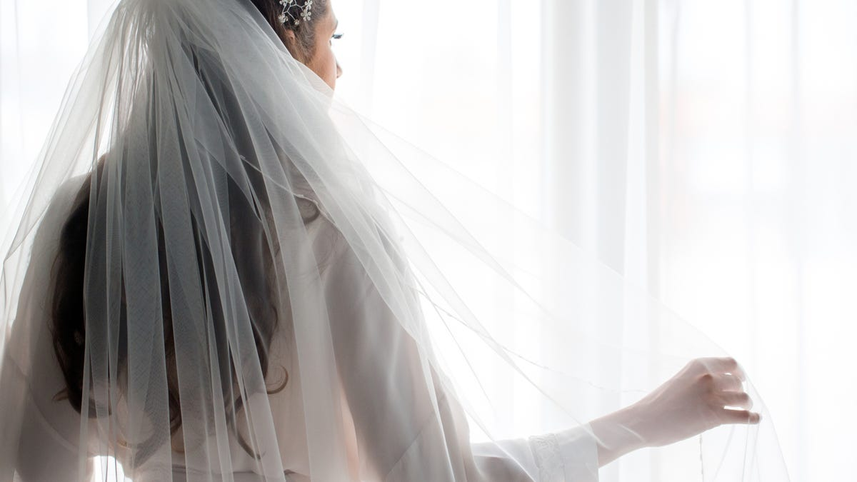 a bride in a robe and her veil looking out a window