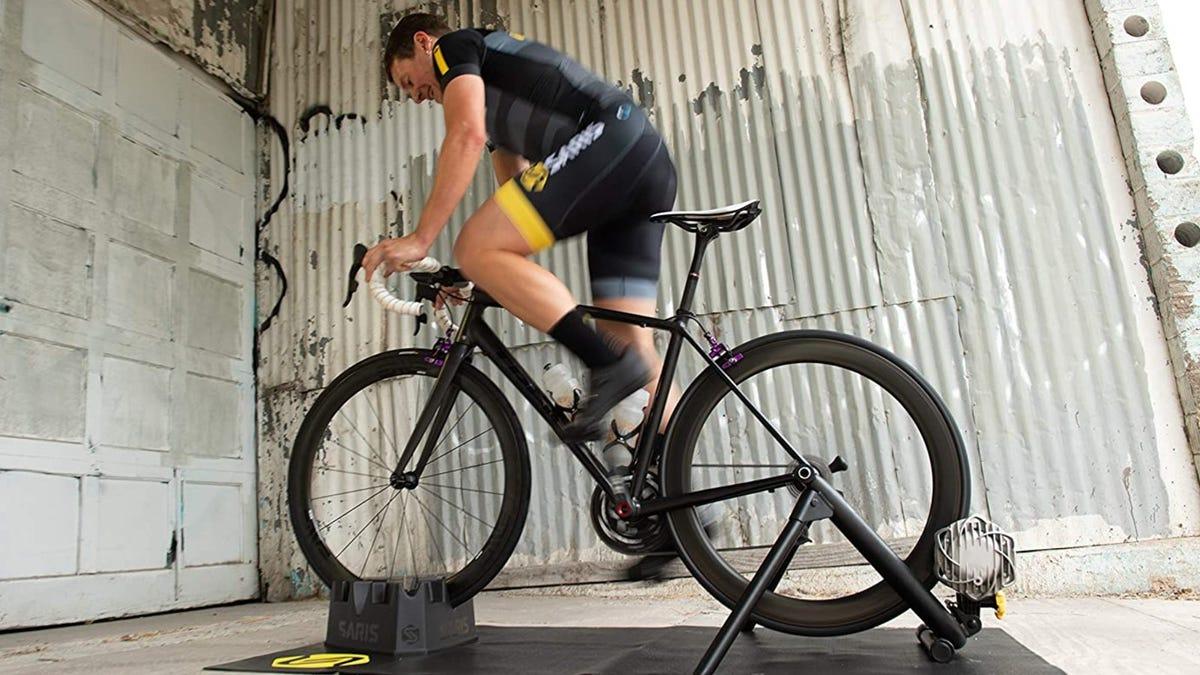 A man riding a bike on a bike trainer in a garage.