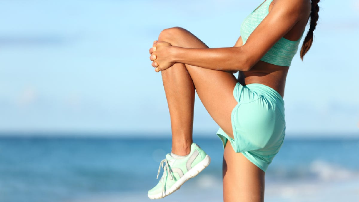 young woman wearing running shorts, a sports bra, and tennis shoes stretching her leg on the beach