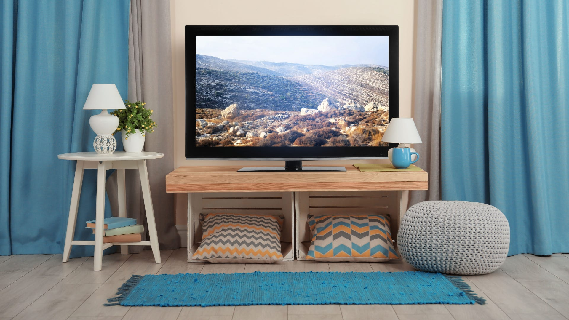 The cozy interior of a living room with a TV on a stand.