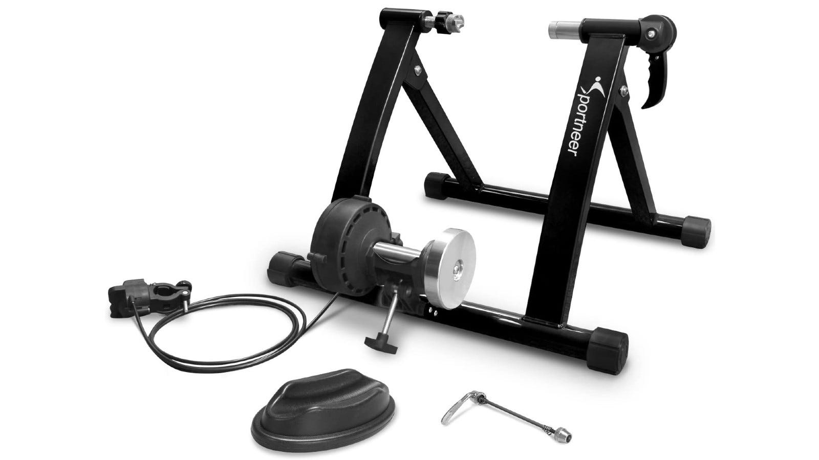 A black bike trainer with its attachments spread in front of it.