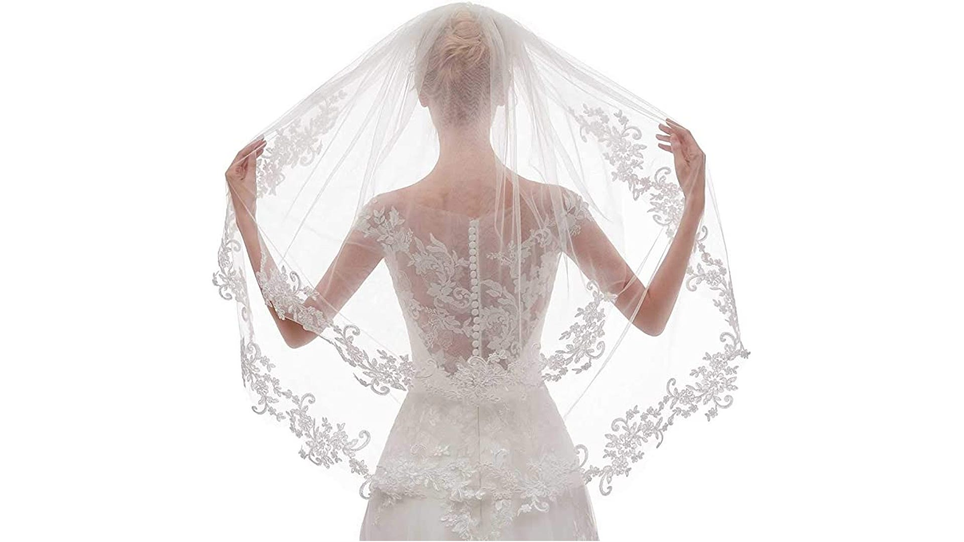 back view of bride displaying wedding veil with patterned floral lace edges