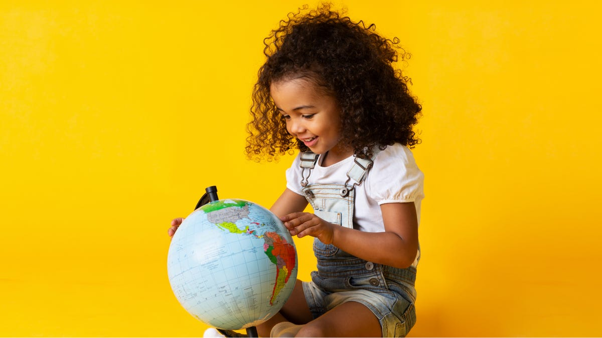 a young girl looking at a globe