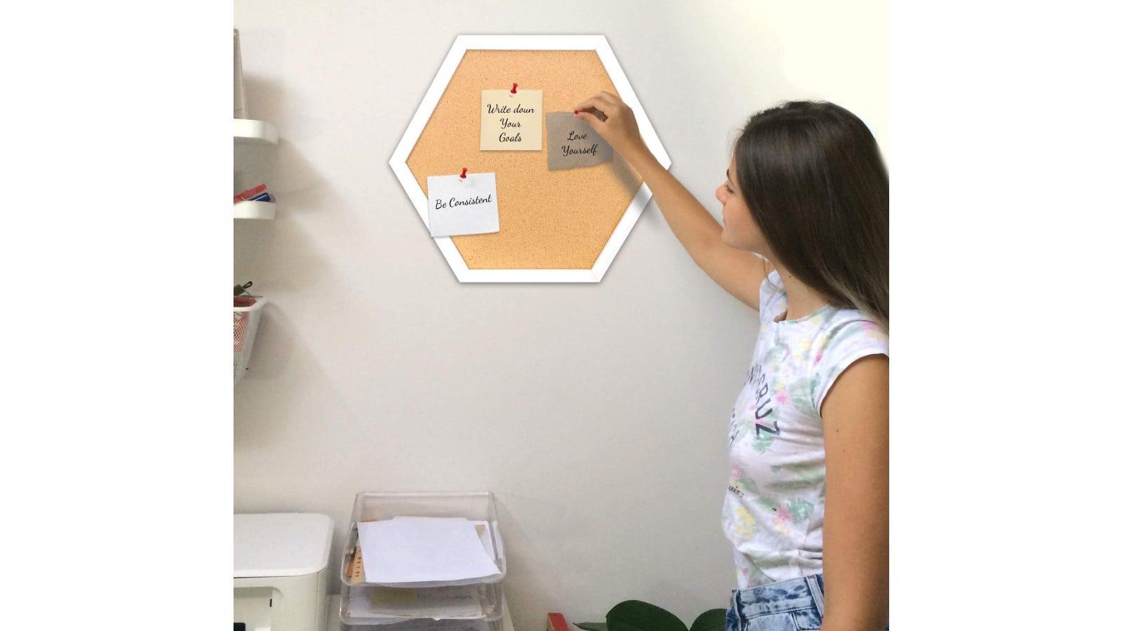 A woman sticking a note to a hexagonal bulletin board.