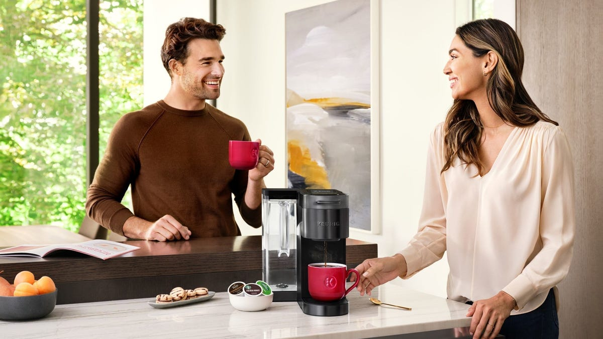 A man and woman stand next to a Keurig machine drinking coffee from red mugs.
