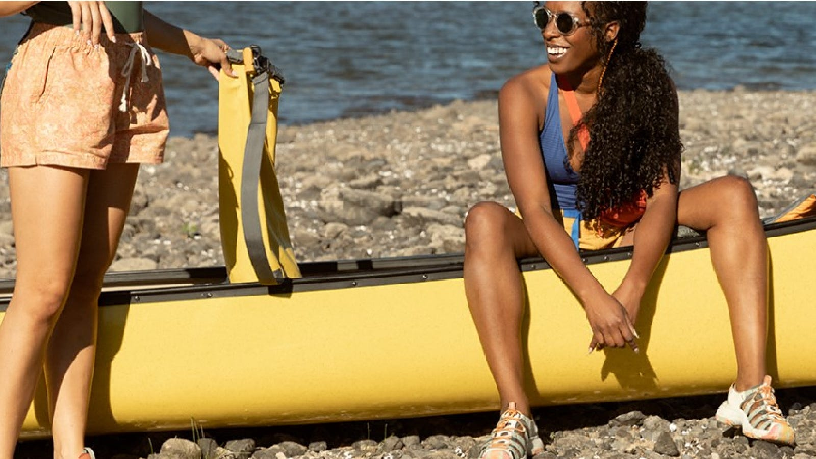 Two women outdoors getting ready to go kayaking, while wearing comfortable Keen hiking sandals.