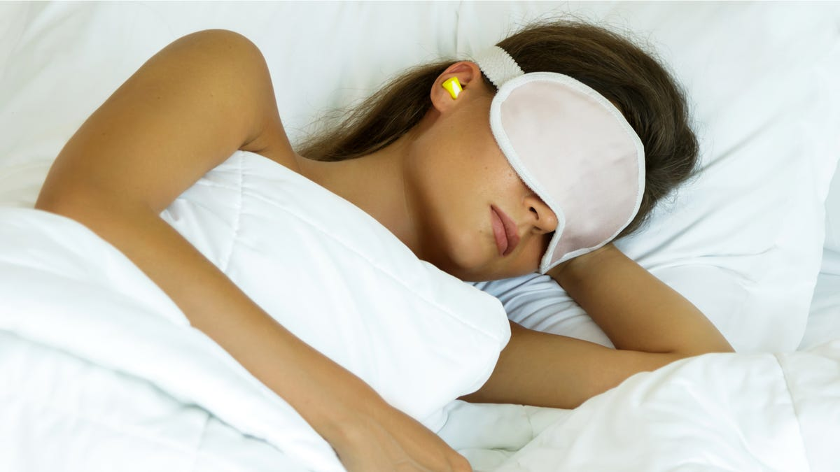 a woman using earplugs and a sleeping mask as she sleeps in a bed