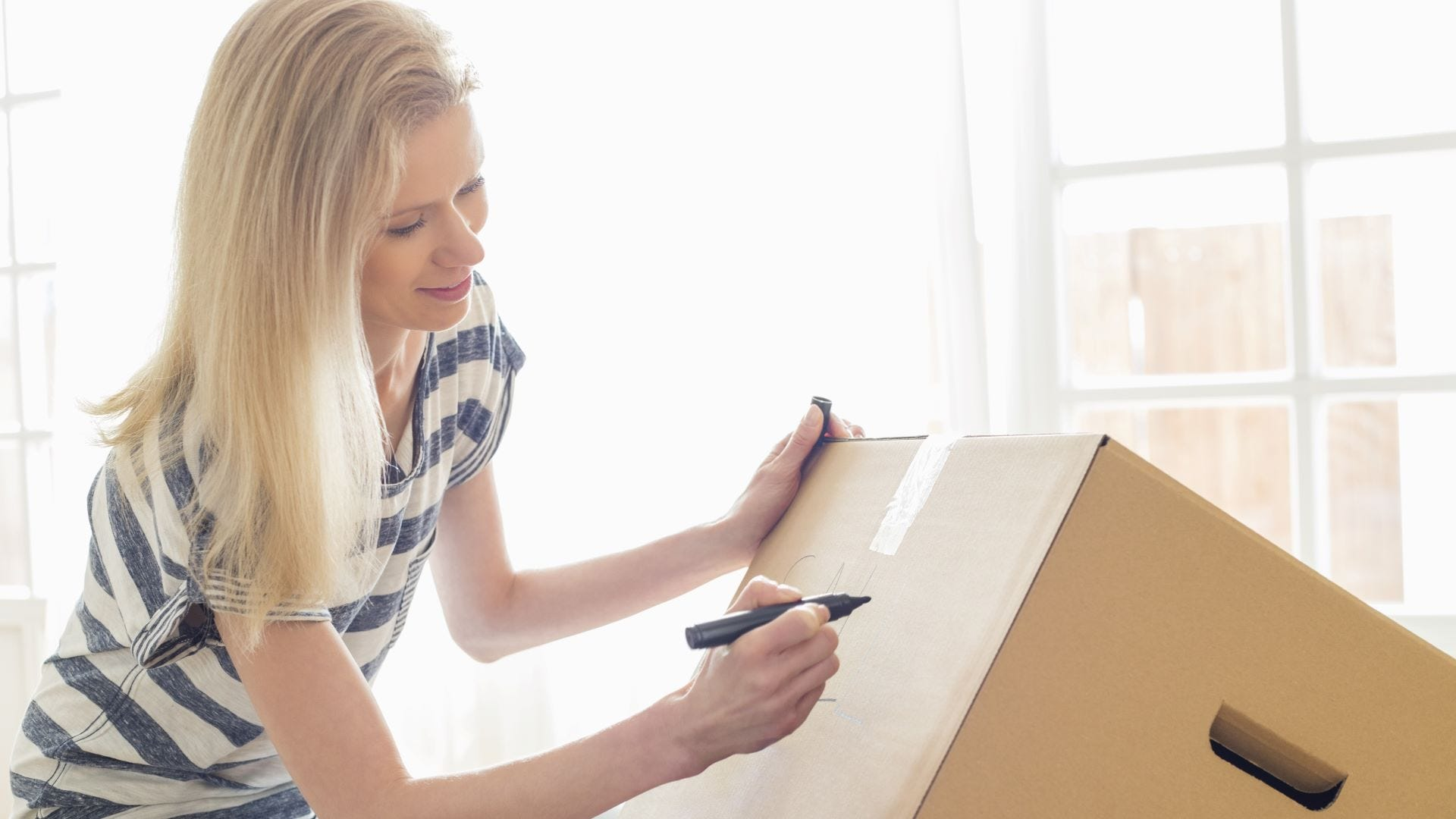 A woman labeling a moving box with a Sharpie.