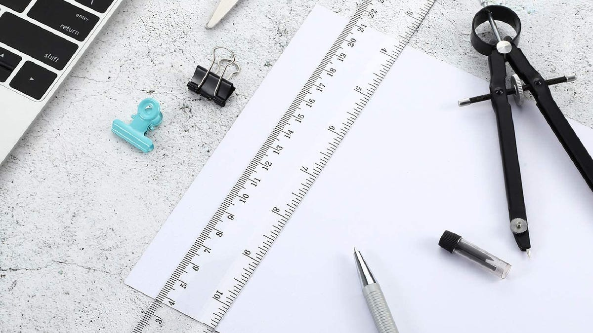 a clear ruler placed on a piece of paper on a desk next to a protractor, pencil, scissors, and a laptop
