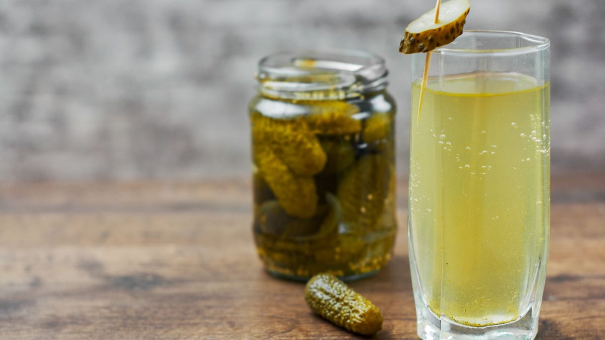 A jar of pickles and a glass of pickle juice.