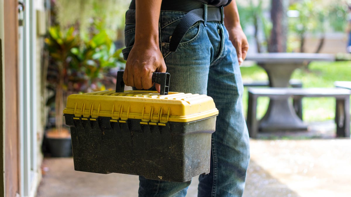 a man holding a tool box with a yellow lid and black bottom