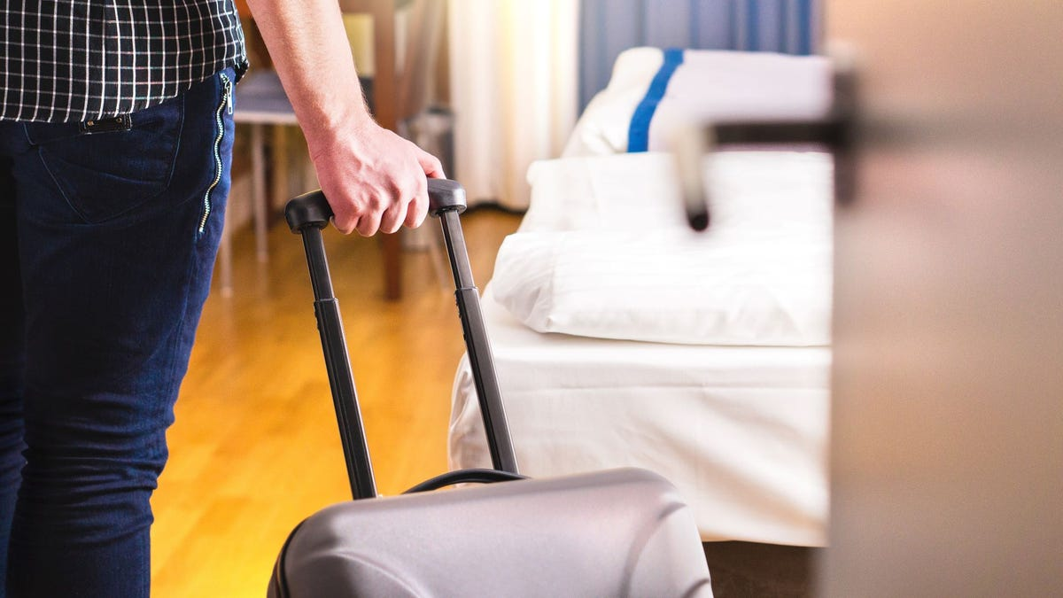 A man pulling a suitcase into a room in a hostel.