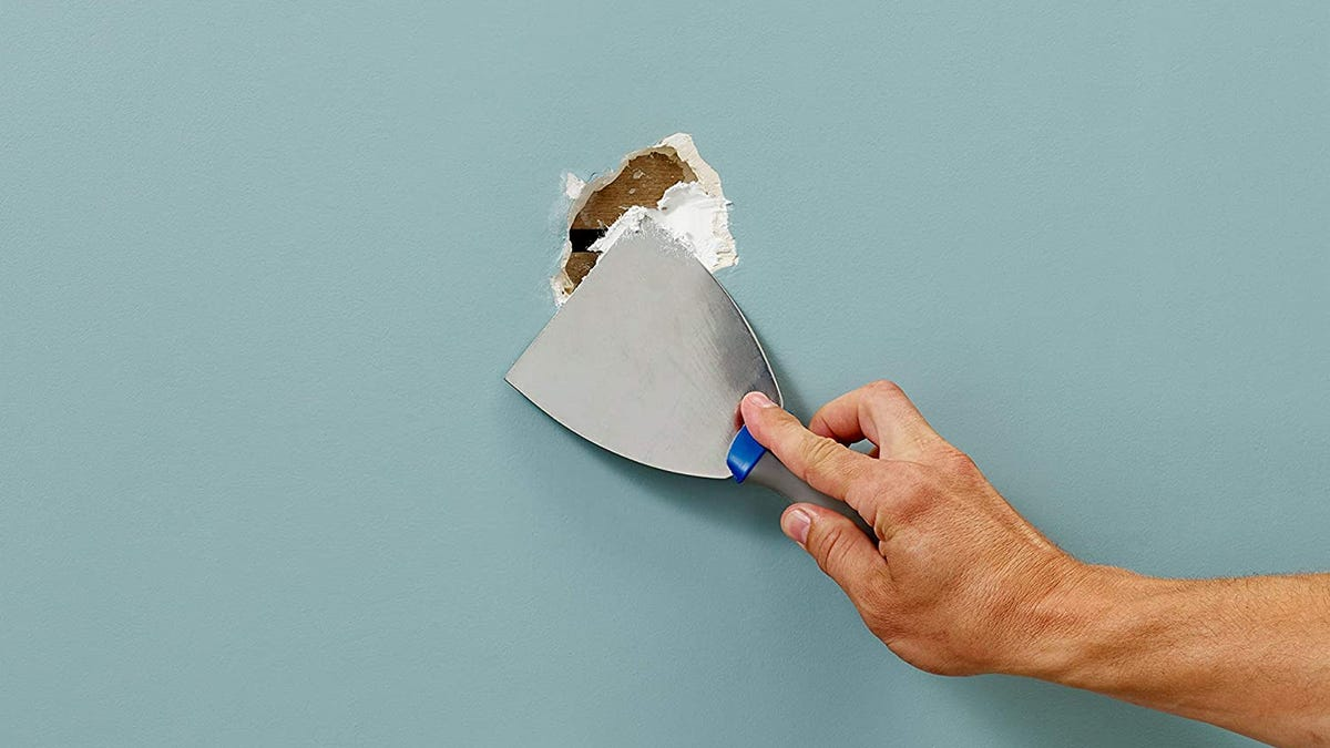 person's hand patching drywall hole with spackling blade on blue wall