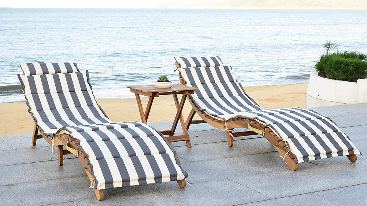 Two striped lounge chairs with table outside at beach.