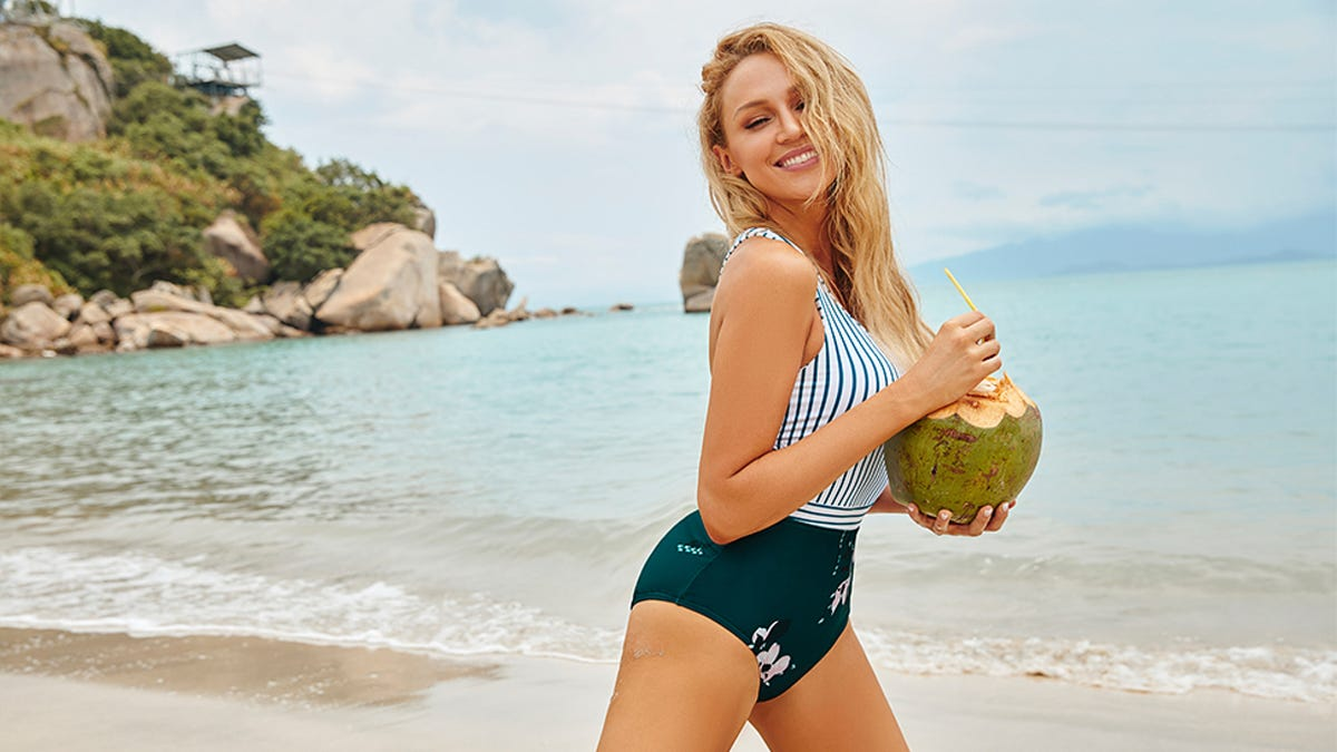 A smiling blonde model on beach in one-piece swimsuit holding coconut drink.