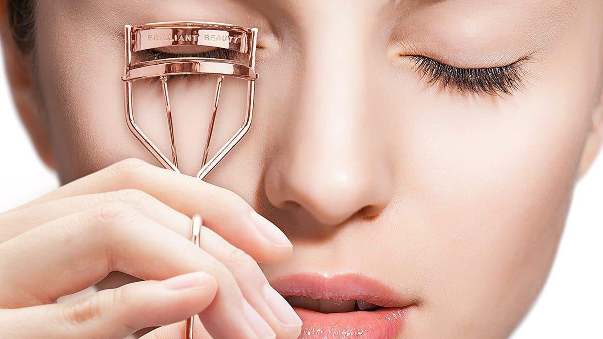 A close up of woman using metal mechanical eyelash curler.