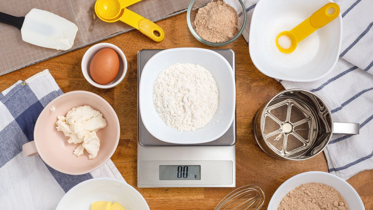Flour on a digital scale, surrounded by dry baking ingredients.