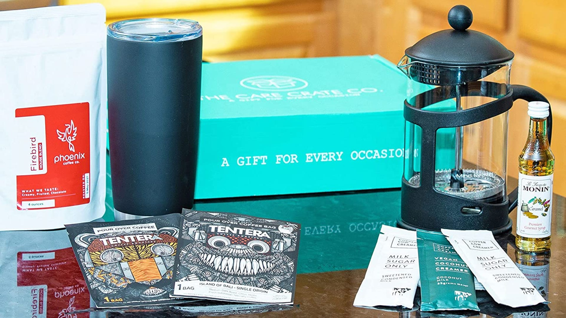 Coffee tools and supplies laid out on a black counter in front of the turquoise box packing.