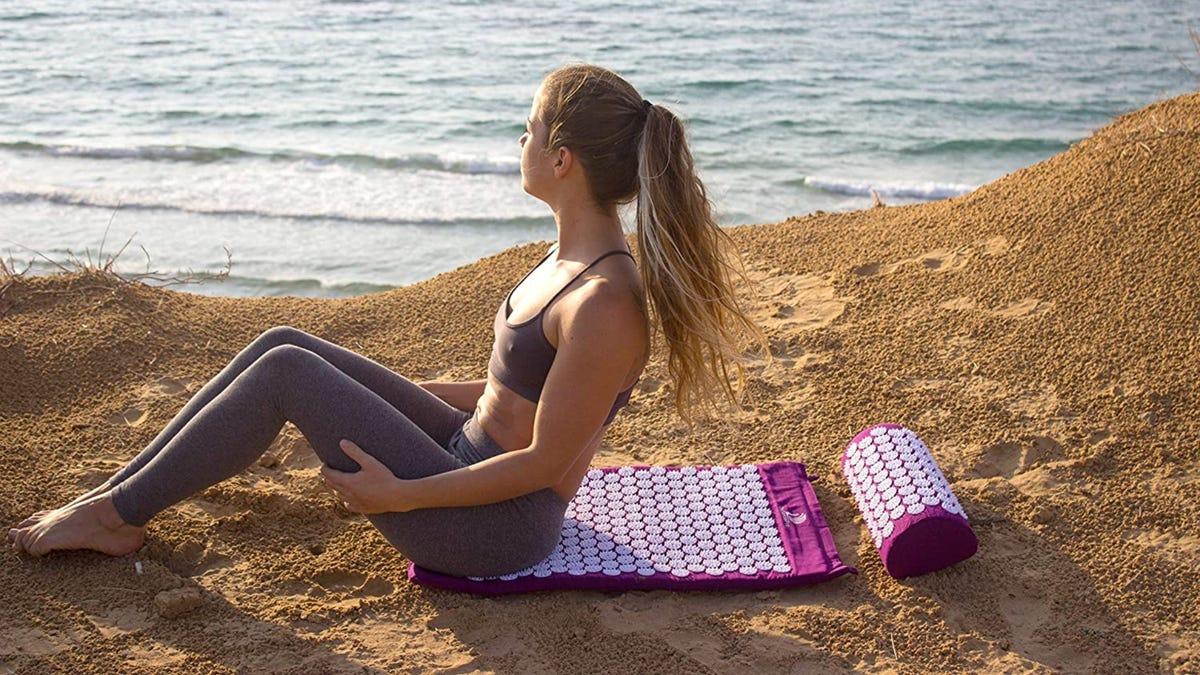A woman sitting on a purple acupressure mat at the beach.