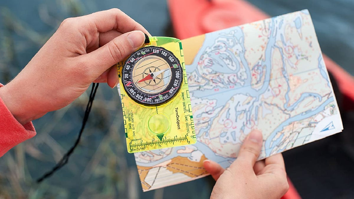 Hands hold a neon green compass and a map outside.