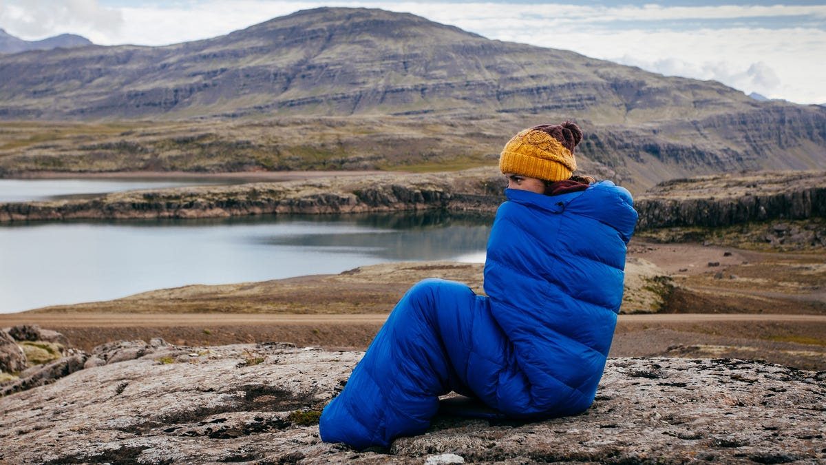 Young woman in warm blue sleeping bag by a lake and mountain