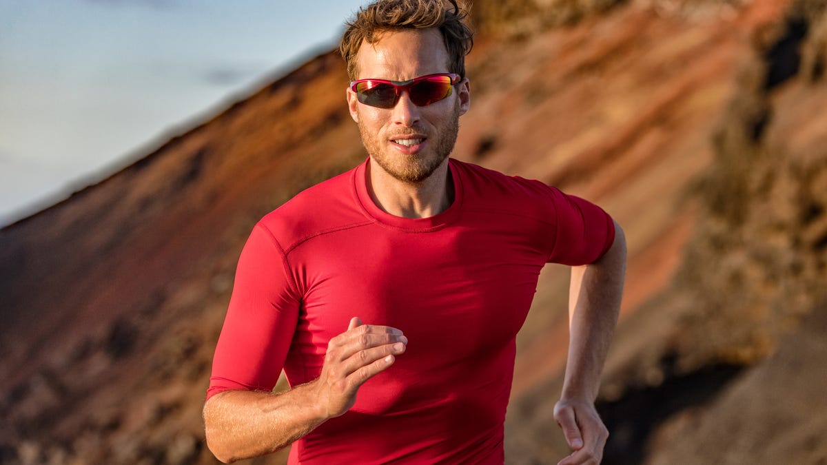 a man wearing sports sunglasses running outside