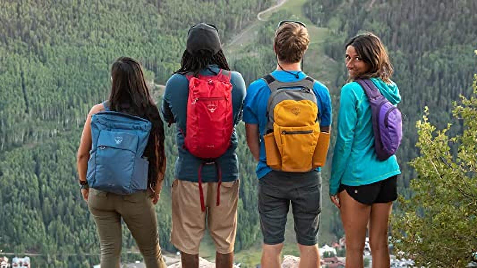 Four hikers wearing various light hiking packs.
