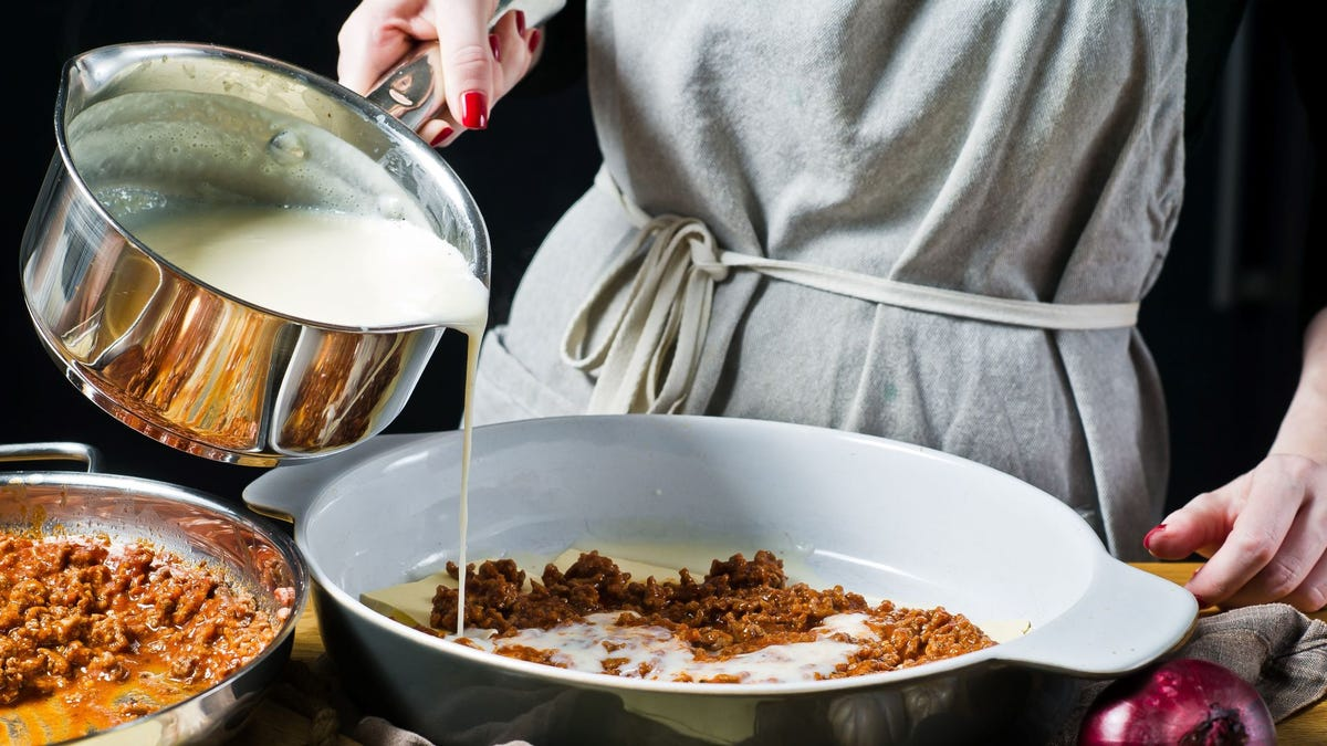 A chef pouring béchamel sauce over meat in a casserole dish.