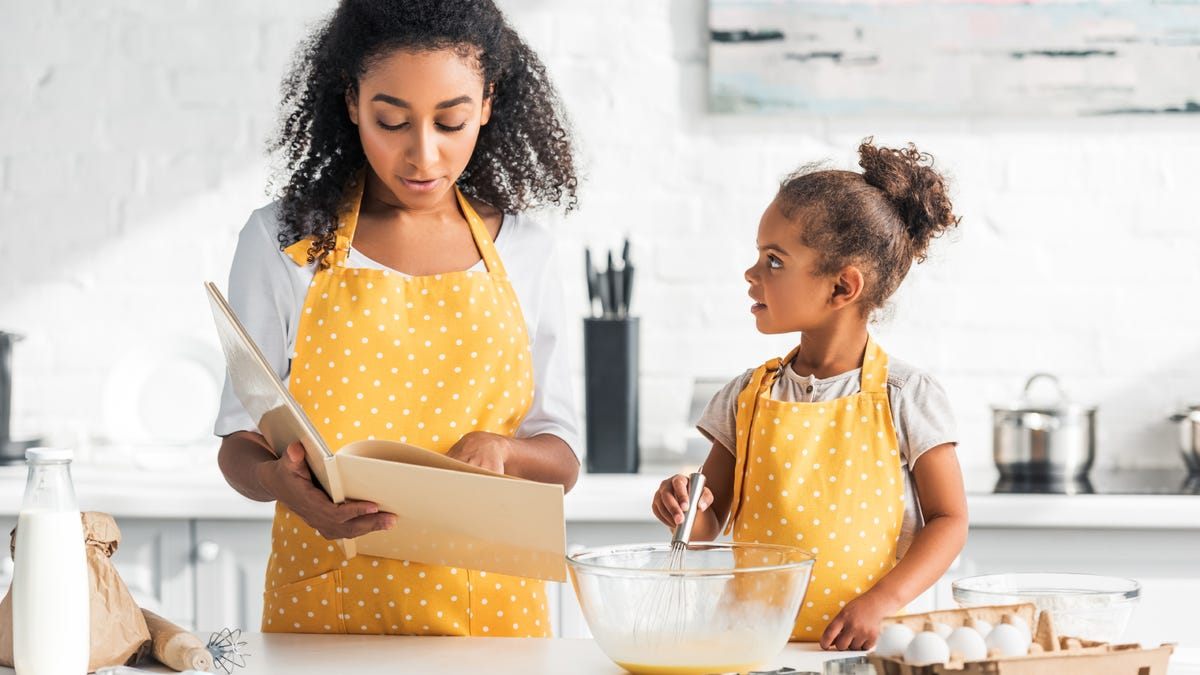 A mother reading a cookbook while her daughter whisks eggs in a kitchen.