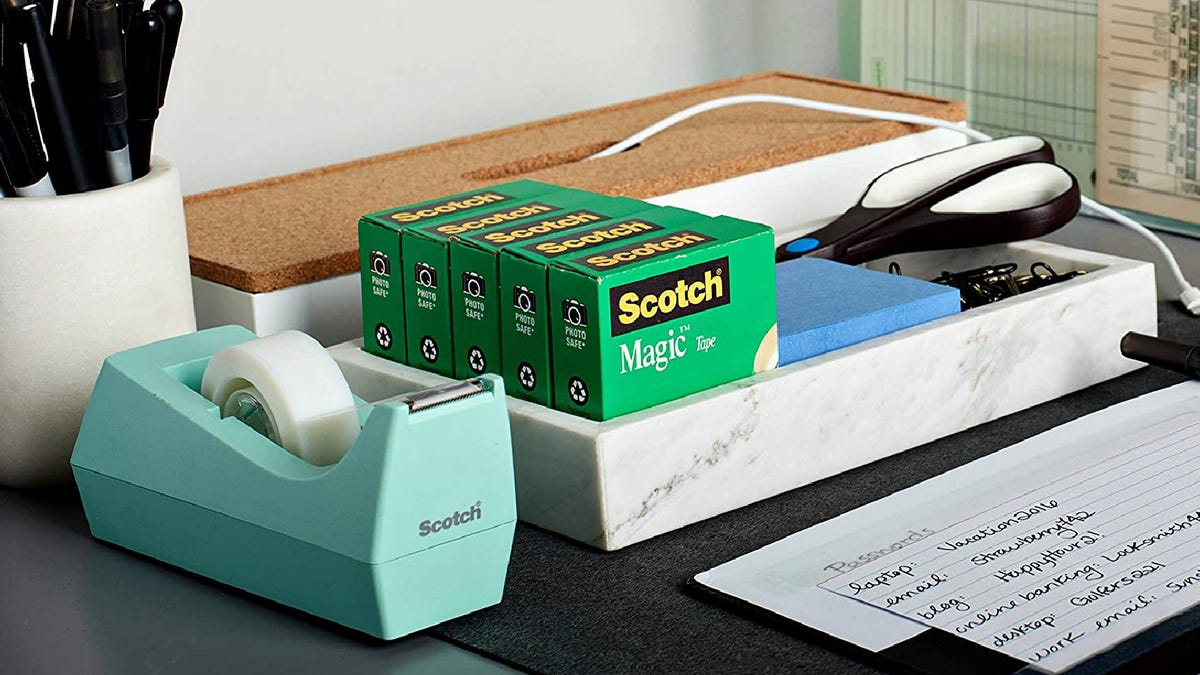 a desk with a blue Scotch tape dispenser and other office supplies
