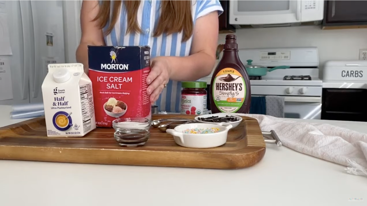 A woman shows the ingredients it takes to make ice cream in a bag.