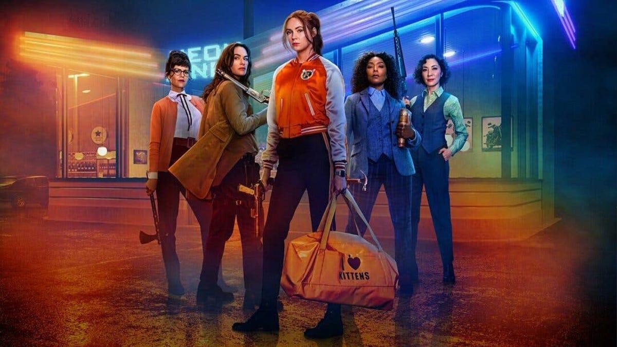 Пять женщин стоят перед закусочной, освещенной голубым и зеленым светом.