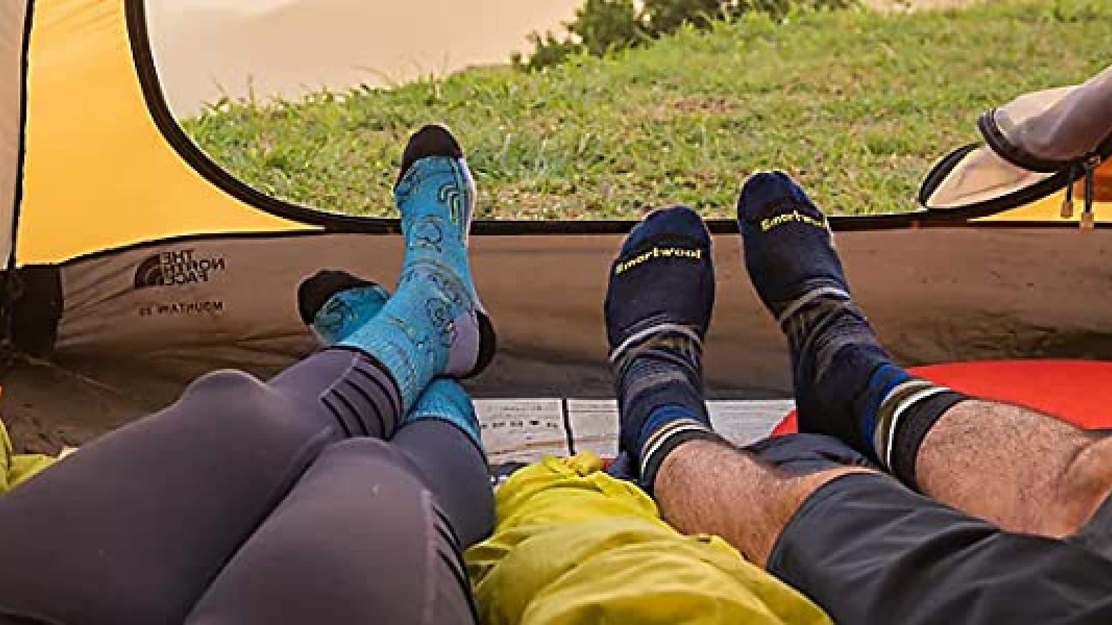 Two hikers enjoying the view form their tend while wearing fresh smartwool socks after a long day outdoors.