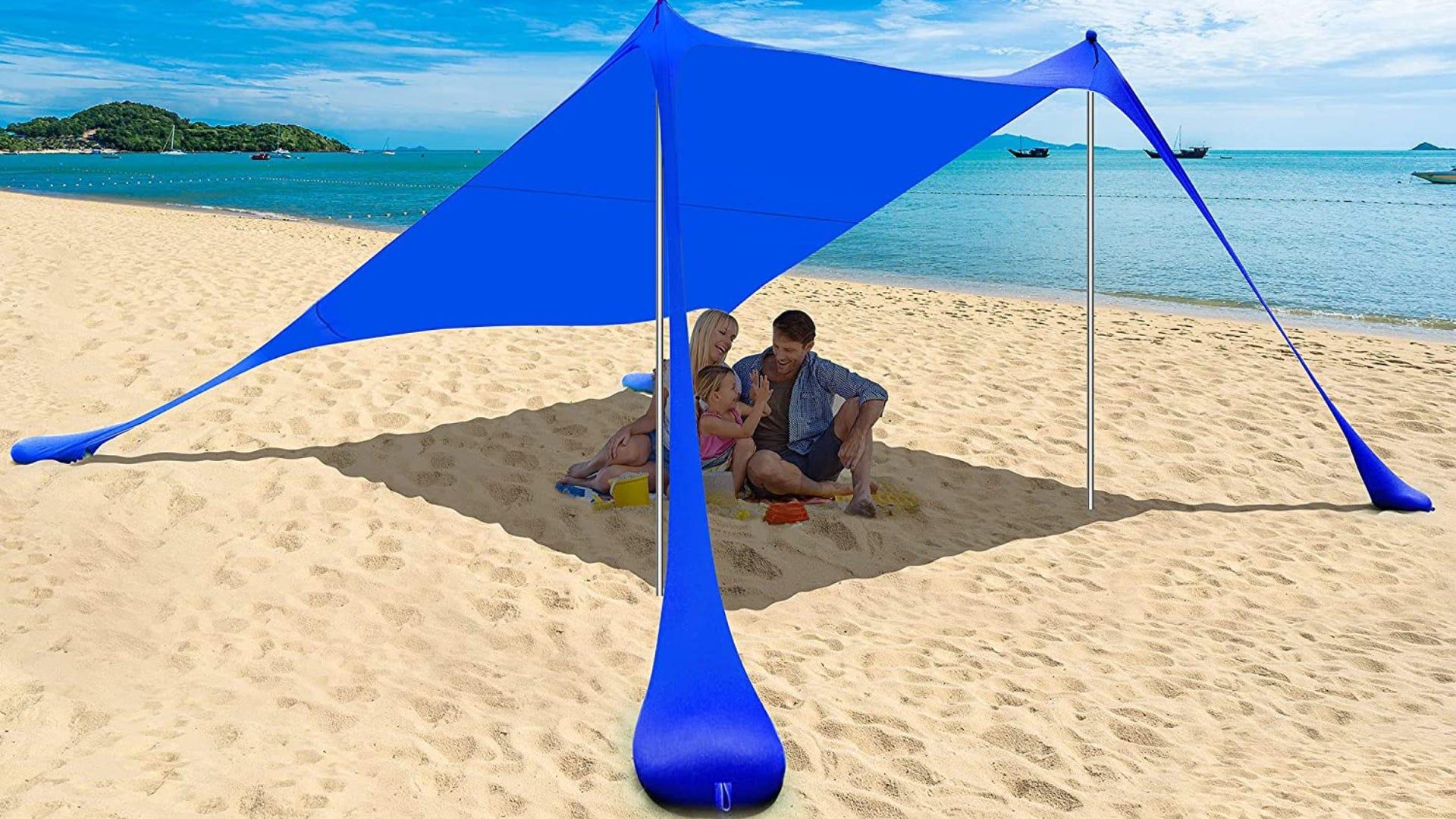 A navy blue canopy with sand anchors shading a family on the beach.