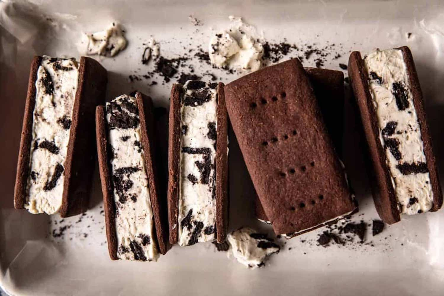 A row of brownie ice cream sandwiches, sitting on their sides, with cookies 'n' cream ice cream