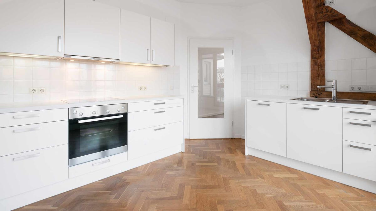 A modern kitchen with a wood floor featuring a herringbone pattern.