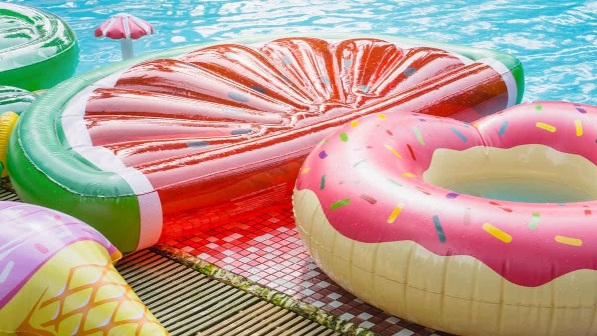 Three pool floats shaped like a watermelon, doughnut, and ice cream cone next to a pool.
