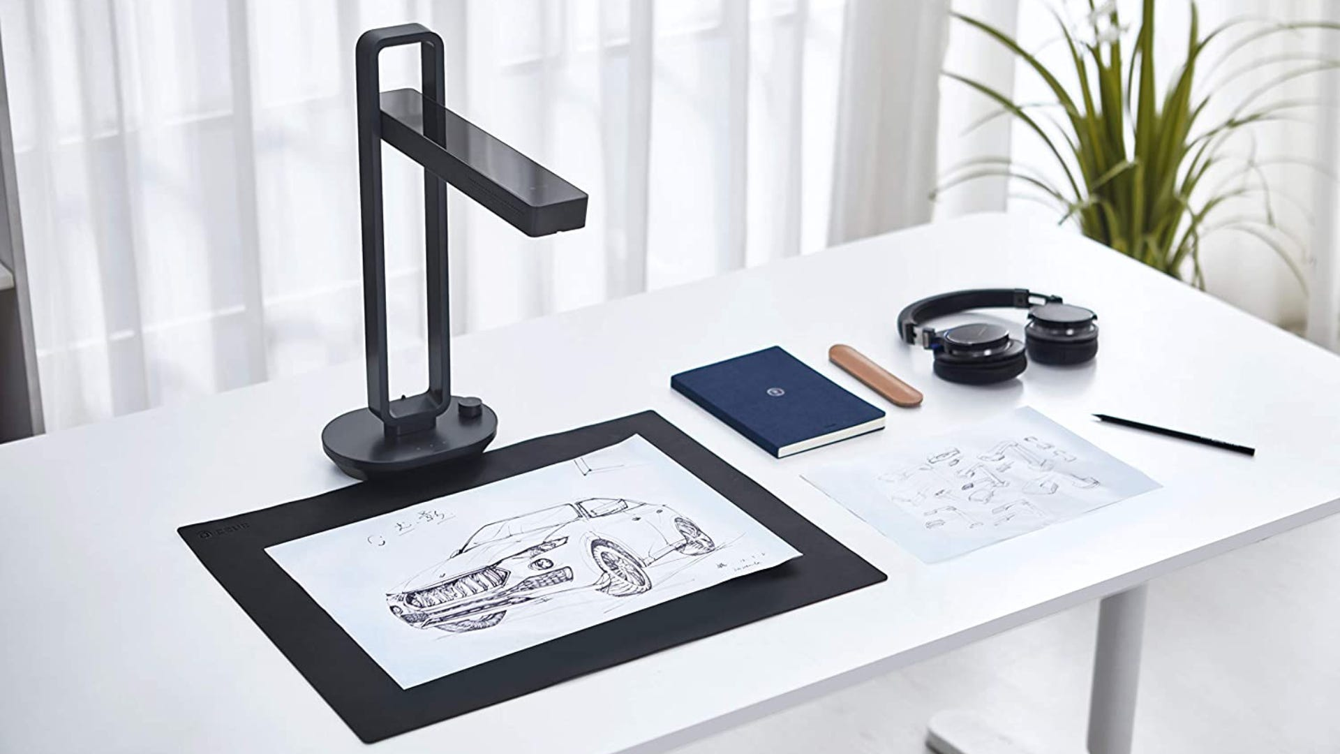 A black document scanner sitting over an art piece on a white desk.