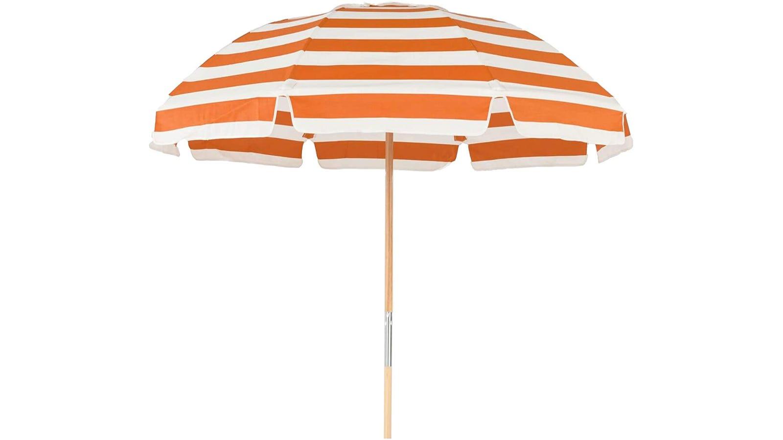 An orange and white striped beach umbrella on a white background