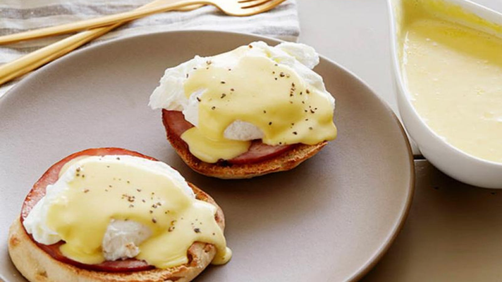 An image of homemade hollandaise sauce poured over hot eggs benedict, with a side of hollandaise