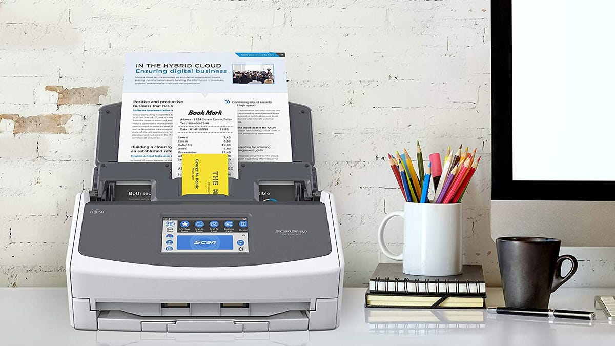 A multi-tray document scanner on a white desk next to a cup of pencils, a mug, and a computer.