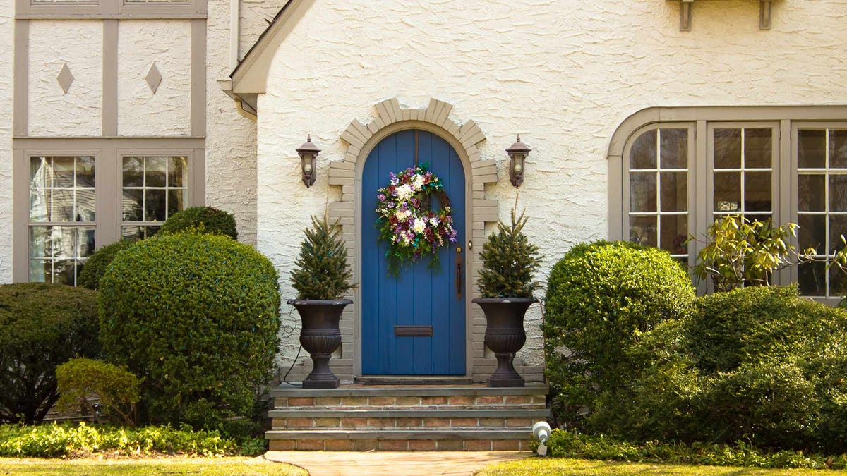 A blue front door on a Tudor-style home.